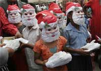 Children at a slum sport Santa hats and face masks as they receive Christmas gifts during a function organized as part of Christmas celebrations by a non-government organization in Bangalore Wednesday.AP