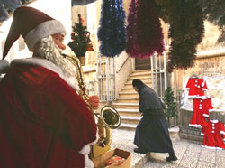 A nun walks past a shop displaying Christmas toys and decoration, in Jerusalem's Old City. AP