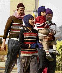A family shields itself against the cold as they walk at India Gate in New Delhi. PTI