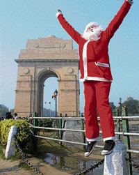 Merrymaking: A man dressed as Santa Claus cheers people during Christmas celebrations at India Gate in New Delhi on Friday. PTI