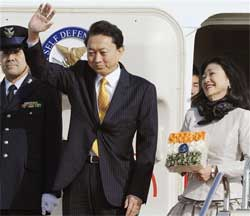Japan's Prime Minister Yukio Hatoyama waves as his wife Miyuki looks on before boarding a special plane at Tokyo's Haneda airport on Sunday Dec. 27, 2009. Hatoyama left for India for talks with his Indian counterpart Manmohan Singh in New Delhi. AP