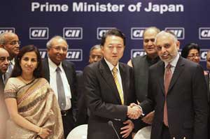 Japanese Prime Minister Yukio Hatoyama, center, shakes hands with Confederation of Indian Industry Vice President Hari S. Bhartia as others look on in Mumbai on Monday. AP