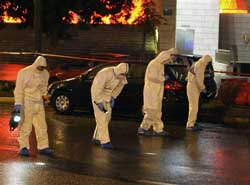 Members of Greece's counter-terrorism squad comb the street for bomb fragments outside the Ethniki Insurance building following a blast, in Athens late Sunday. AP