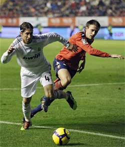 Real Madrid's Sergio Ramos, left, duels for the ball with Osasuna's Ignacio Monreal during their Spanish La Liga soccer match at the Reyno de Navarra stadium in Pamplona, northern Spain on Sunday. AP