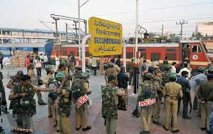 Police personnel stand next to the Hyderabad-Delhi Andhra Pradesh Express train, following rail roko agitations called by the Telangana Joint Action Committee (JAC) of students, at a railway station in Secunderabad on January 5, 2010. All political leaders from the state of Andhra Pradesh were called for a crucial meeting to be held in Delhi with Union minister P. Chidambaram on the contentious issue of Telangana. (AFP)