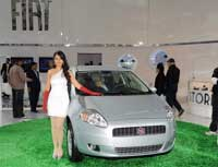 A model poses in front of a Fiat Punto car during the 10th Auto Expo in New Delhi on Tuesday. AFP Photo