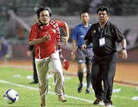 Watch me! Hendri Mulyadi dribbles away as Indonesia's coach Benny Dolo looks on in Jakarta on Thursday. AP