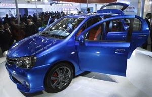 Photo Go to Article Onlookers stand next to Toyota's compact car 'Etios' at the 10th Auto Expo in New Delhi . Reuters