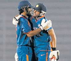 Well done, skip: MS Dhoni gets a pat on the back from Suresh Raina after reaching his ton. Reuters