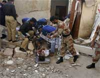 Pakistani police officer and volunteers remove a dead body at a site of the explosion in Karachi, Pakistan on Friday. AP