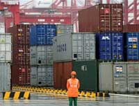A worker stands in front of containers at the newly open Yangshan deep water port in this Dec. 10, 2005 file photo taken in Shanghai, China. AP