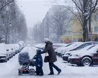 A woman and her children cross a street during a heavy snow fall in Berlin, Germany, on Saturday. AP