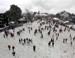 Tourists enjoying with snow after season's first snowfall in Shimla on Wednesday. PTI