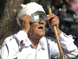 An old man takes a view of the solar eclipse in Surat on Friday. PTI