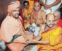 Paryaya Shiroor Mutt seer Lakshmivarateertha ascending the Sarvajna Peetha, assisted by the outgoing Paryaya pontiff Puttige Mutt's Sugunendrateertha at Krishna Mutt in Udupi on Monday. dh photos