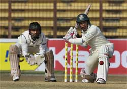 Bangladesh's Mushfiqur Rahim prepares to bat as Indian wicketkeeper Dinesh Karthik looks on during the third day of the first cricket test match between Bangladesh and India in Chittagong. AP