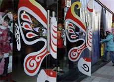 A woman walks past Chinese traditional motifs used to attract shoppers outside a store in Beijing, China on Thursday. AP