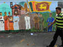 A Sri Lankan man walks past a wall painting depicting the country's multi-cultural and multi-religious life in Colombo on Thursday. AFP