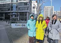 Women in colourful jackets walk past the Google sign outside the Google's China headquarters in Beijing on Friday. AP