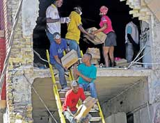 Saving the remains: Workers remove items from a hardware store in downtown Port-au-Prince, Haiti, on Thursday. The owners of the store are trying to salvage their inventory  from looters. AP