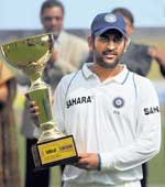 PROUD MAN:  MS Dhoni poses with the trophy after winnng the Test series against Bangladesh on Wednesday. REUTERS