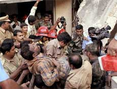 Rescuers carry a man from the debris of a collapsed building in Thiruvananthapuram on Monday. Around 15 people were feared to be trapped in the building. PTI
