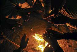 People huddle around the fire to escape the Delhi chill.