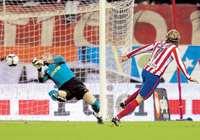 On target: Atletico Madrid's Diego Forlan scores the opening goal past Barcelona's goalkeeper Victor Valdes during their  Spanish League fixture on  Sunday. AFP