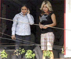 Foreign tourists watching the blast site at German Bakery from a nearby building in Pune on Monday. PTI