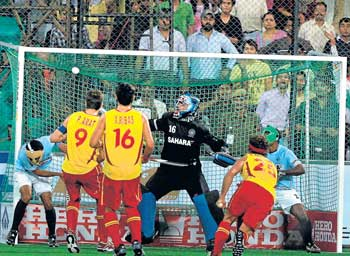 Pau Quemada (second from right) scores Spain's final goal during their 5-2 drubbing of India in the World Cup in New Delhi on Thursday. PTI