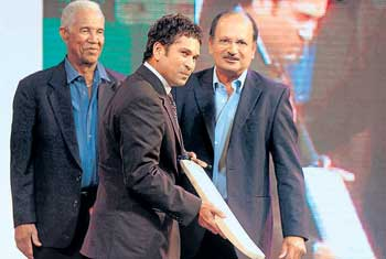 Sachin Tendulkar (centre) is presented with an autographed bat as West Indian great Garry Sobers (left) and former India captain Ajit Wadekar look on. PTI