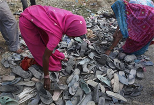 Women looking for missing relatives scan sandals after a stampede at an ashram in Kunda, 180 kilometers (112 miles) southeast of Lucknow, UP on Thursday.  AP