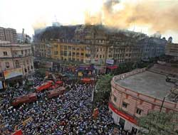 Local people gather on the road as fire personnel douse a major fire fire that broke out at a multi-storeyed building on Park Street in Kolkata on Tuesday. PTI