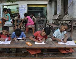 Children attend a school set up on a footpath in Ahmedabad on Friday, April 2, 2010. The footpath school is run by 62-year-old Kamal Parmar who started giving evening classes to children, mostly from slum areas, more than ten years ago. AP
