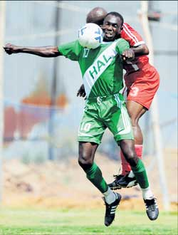 HASC's Fredrick Okwagbe (foreground) battles for possession with Malabar United's Emmanuel Ajaawa in the I-League Division II match in Bangalore on Monday. DH PHOTO