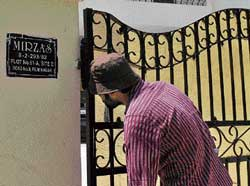 Looking through: A journalist peeps through the gate of Sania Mirza in Hyderabad. Sania and Shoaib remained indoors on Thursday while family members went shopping. AFP