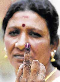 A Sri Lankan voter shows her inked finger after voting at a polling station in Colombo on Thursday. AFP