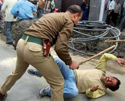 A policeman beats one of the striking government employees during a protest march at Regal Chowk in Srinagar on Saturday. PTI Photo
