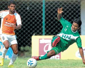 ROCK SOLID: Ricky Joy of HASC (right) clears a ball from the reach of Golden Threads' Sanjay Vennara in the I-League II Division match on Sunday. DH photo