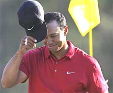 Tiger Woods tips his cap on the 18th green after finishing his final round of the Masters golf tournament in Augusta on Sunday. AP