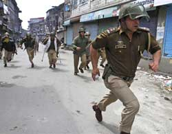 Police officers chase protesters, unseen, during a a general strike called by hardline faction of Hurriyat Conference in Srinagar, on Tuesday. AP Photo