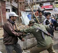 A policeman charging on a striking goverment employee during a protest march at Lal Chowk in Srinagar on Monday. PTI Photo