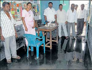 Government Lower Primary School at Gangammanapalya flooded with drain water on Wednesday due to heavy rains in Kolar on Tuesday. Teachers Saroja, Ramaiah, Chandrashekar, S Srinivas and others are seen. DH Photo