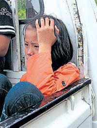 A girl reacts as she sits in the back of a pick-up truck at the site of an explosion in Yangon on Thursday. AFP