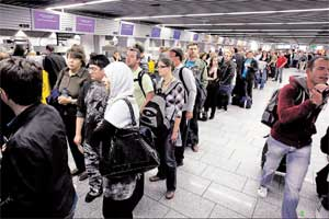 Stranded: Passengers stand in a queue at a ticket counter at Frankfurt airport in Germany on Friday. REUTERS
