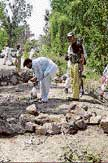 Police officers and rescue workers gather at the site of a suicide bombing in Kuccha Pakka area in Pakistan on  Saturday. AP
