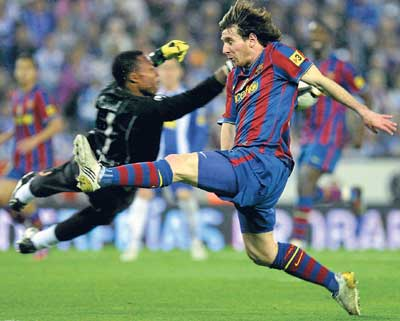 TIMELY TACKLE Espanyol goalkeeper Carlos Kameni clears the ball from the reach of Barcelona's Lionel Messi. AFP