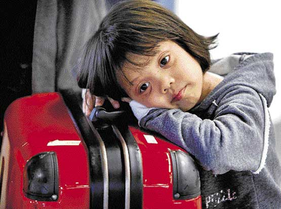Long wait: A girl rests on her suitcase in a terminal at the airport in Frankfurt, central Germany, on Sunday. AP