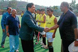 Lokayukta Justice N Santhosh Hegde shakes hands with umpire Venu Utthappa prior to SAI-Canara Bank match. Canara Bank team players and Coorg Hockey Association President Mohan Ayyappa look on.