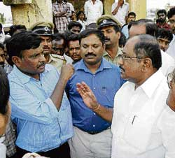 OF DEVELOPMENT AND HUMANITY Additional Deputy Commissioner G S Nayak and legislator K P Bache Gowda in a heated argument over eviction of families from Basappa choultry in Chikkaballapur on Friday. DH Photo